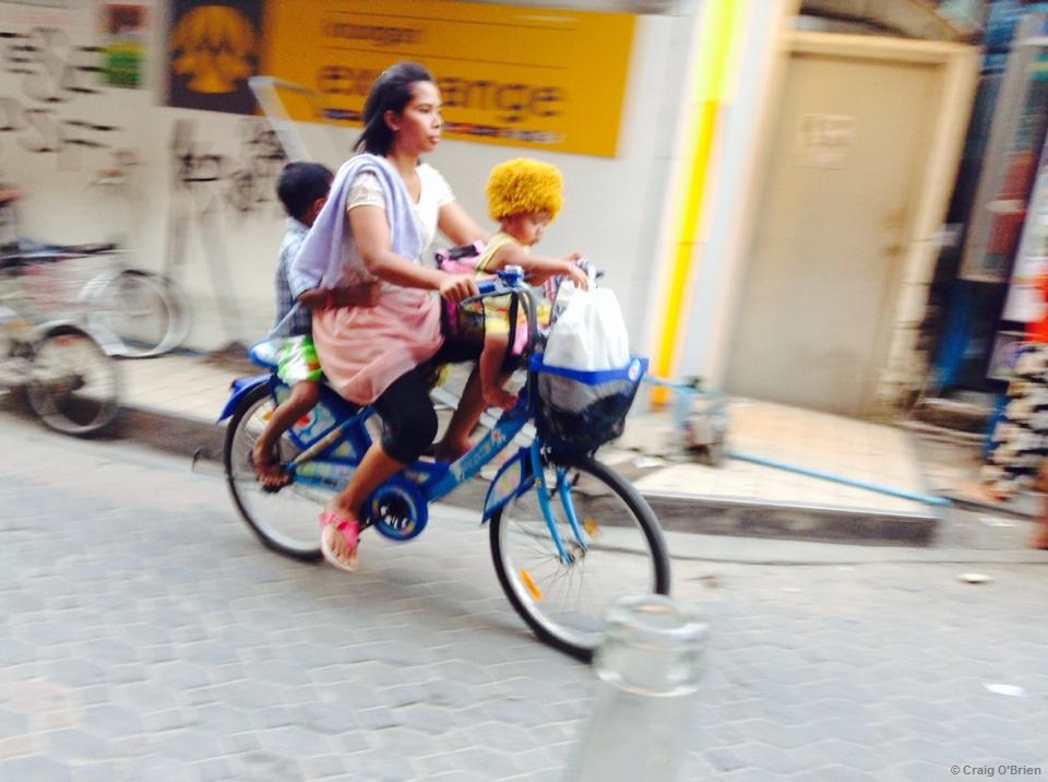 A woman riding with her children on a busy sidewalk on one of the Thai islands.